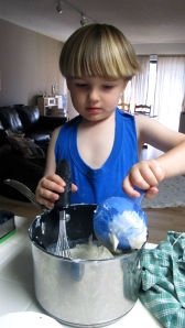 "Eli helping me make play dough. He mixed for about 20 minutes using all utensils in his reach. Yep, he needed an apron... especially during this phase where everything becomes an instant ""construction site""."